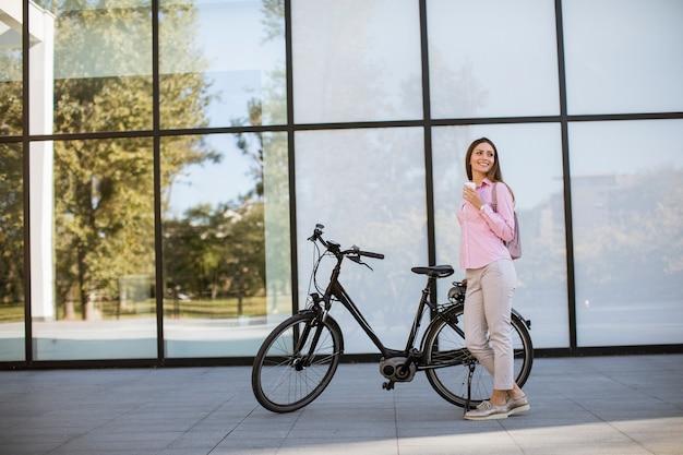 Bela jovem ciclista feminina bebe café quente de um copo pela bicicleta elétrica no ambiente urbano