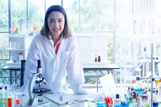Bela jovem cientista trabalhando e se sentir feliz no laboratório