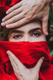 Bela jovem coberta de lenço vermelho pelas mãos do homem