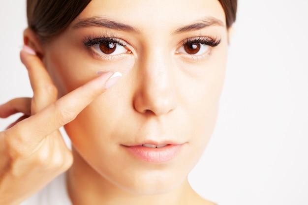 Bela jovem coloca lentes de contato para a visão