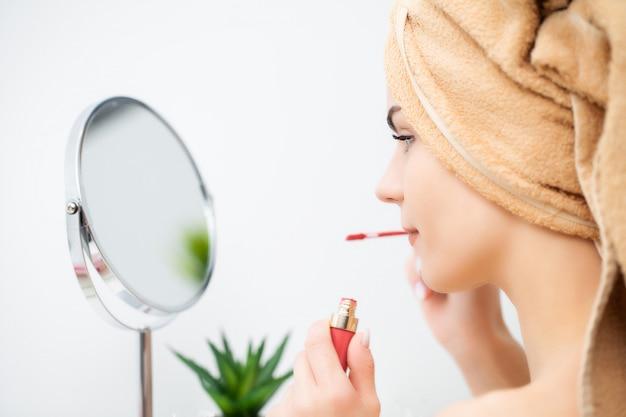 Bela jovem coloca maquiagem no rosto no banheiro