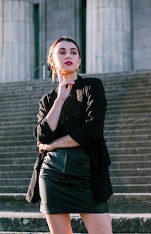 Bela jovem com a mão no queixo em frente a escadarias