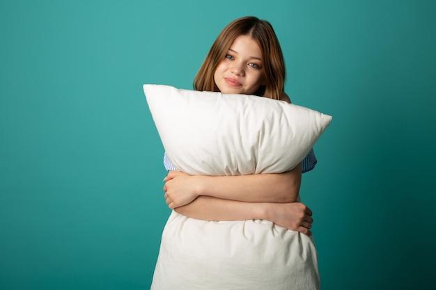 Bela jovem com almofada branca sobre fundo verde Foto Premium