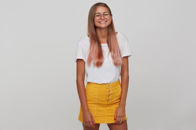 Bela jovem com cabelo comprido castanho claro, mantendo as mãos ao longo do corpo enquanto está de pé sobre uma parede branca, está de bom humor e sorrindo alegremente