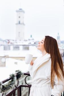 Bela jovem com cabelo comprido em roupão de banho, bebendo chá na varanda. manhã de inverno perfeita. bela vista da cidade.