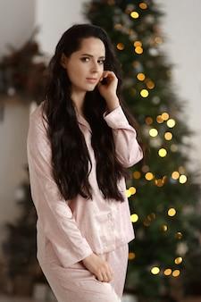 Bela jovem com cabelo escuro, vestindo pijamas da moda se passando perto da árvore de natal decorada.