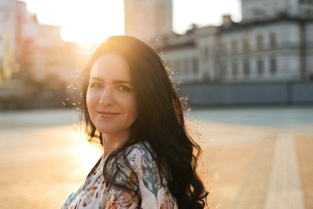 Bela jovem com cabelo longo cacheado veste camisa andando na rua da cidade, aproveitando o tempo ensolarado. espaço para texto