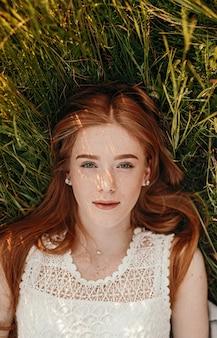 Bela jovem com cabelo ruivo e sardas deitada na grama