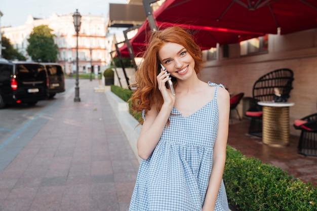Bela jovem com cabelos longos, falando no celular
