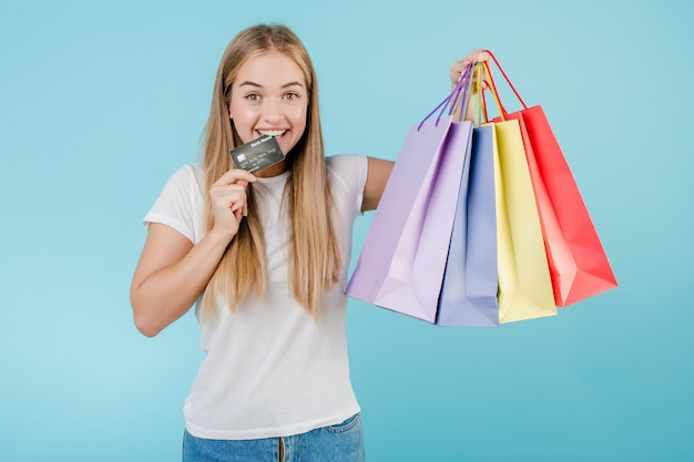 Bela jovem com cartão de crédito e sacolas coloridas isoladas sobre azul