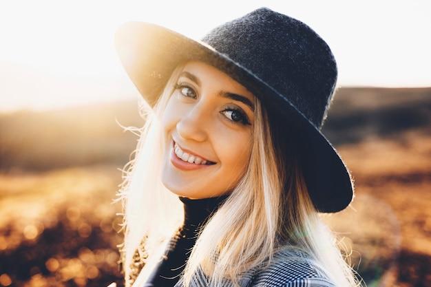 Bela jovem com chapéu estiloso, sorrindo alegremente e olhando para a câmera em pé no fundo desfocado da natureza outono em dia ensolarado.