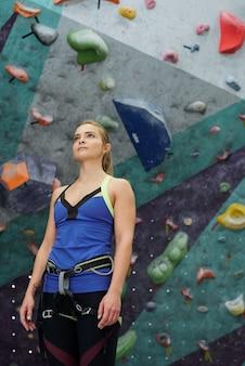 Bela jovem com cintos de segurança na cintura e quadris em pé contra uma parede de escalada com pequenas pedras artificiais na academia