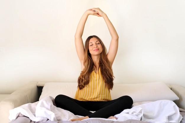 Bela jovem com corpo magro e magro fazendo ioga na cama com os olhos fechados.