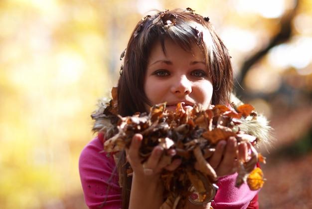 Bela jovem com folhas caindo na floresta de outono