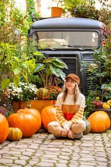 Bela jovem com folhas coloridas de outono e abóboras