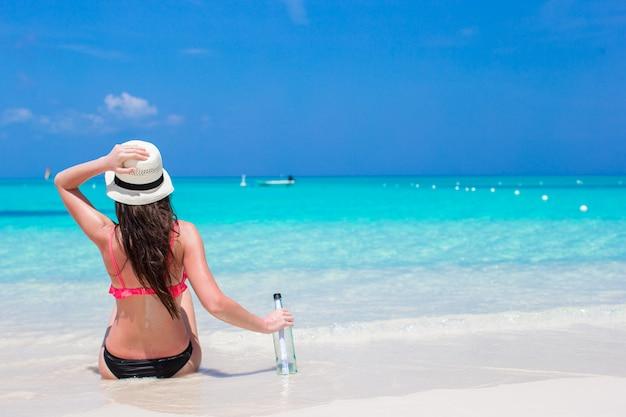 Bela jovem com garrafa sentado na praia