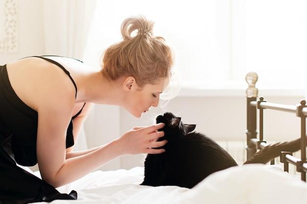 Bela jovem com gato preto em cobertor em quarto branco