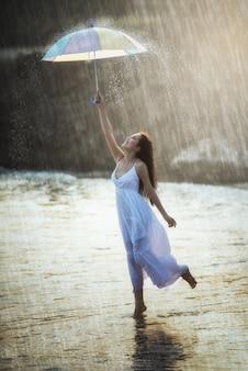 Bela jovem com guarda-chuva de arco-íris, sob a chuva de verão