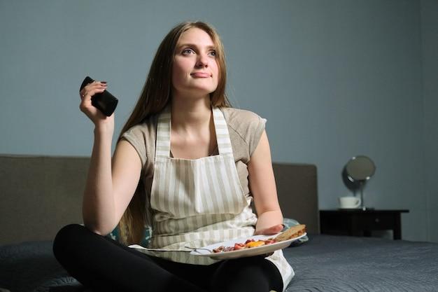Bela jovem com interesse assistindo tv e comendo, mulher sentada na cama com comida caseira fresca, com controle remoto, relaxando em casa