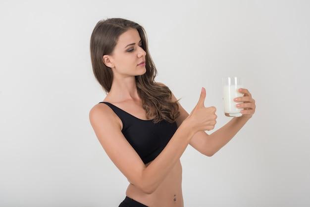 Bela jovem com leite de vidro