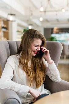 Bela jovem com maquiagem profissional e penteado sentado no restaurante.