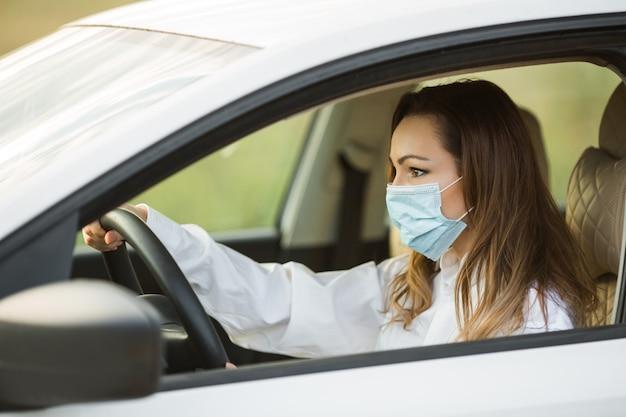 Bela jovem com máscara médica dirigindo um carro