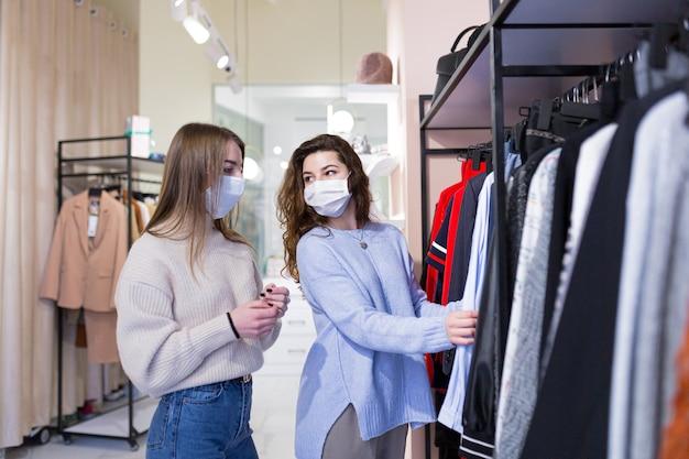 Bela jovem com namorada fazendo compras seguras em loja de roupas durante uma pandemia com máscaras