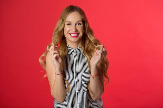 Bela jovem com o cabelo em uma parede vermelha