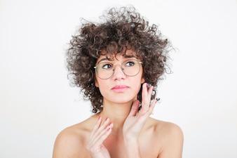 Bela jovem com óculos contra o pano de fundo branco