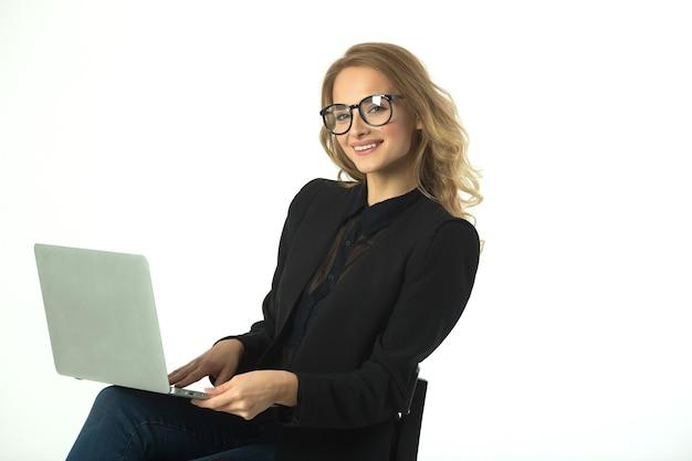 Bela jovem com óculos em um terno preto com um laptop em uma parede branca