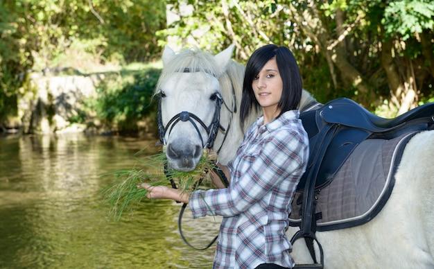 Bela jovem com passeios a cavalo branco no rio