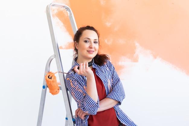 Bela jovem com rolo de pintura dentro de casa. redecoração, reforma, conserto de apartamentos e
