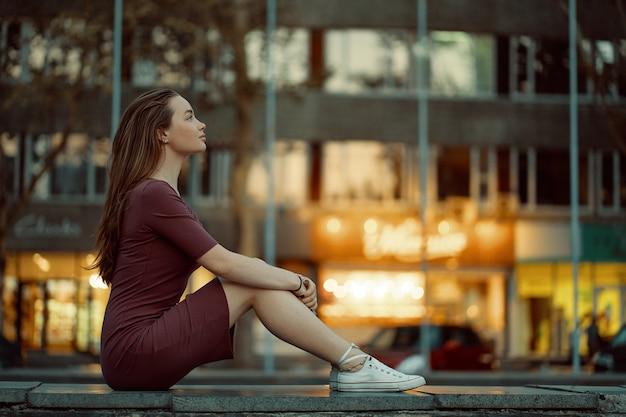 Bela jovem com rosto de conto de fadas apresenta com luzes da cidade