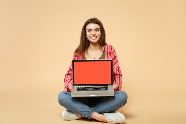 Bela jovem com roupas casuais, sentado, segurando o computador laptop pc com tela em branco vazia isolada em fundo bege pastel. emoções sinceras de pessoas, conceito de estilo de vida. simule o espaço da cópia.