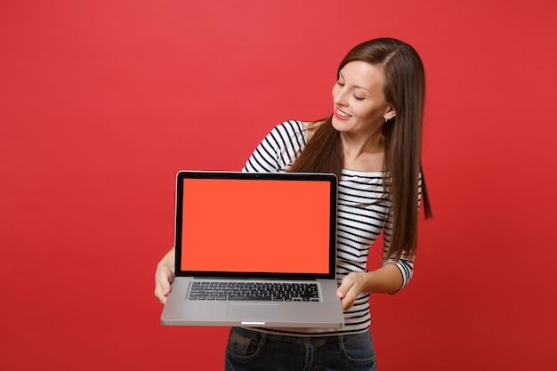 Bela jovem com roupas listradas, olhando no computador laptop pc com tela vazia preta em branco nas mãos isoladas sobre fundo vermelho. emoções sinceras de pessoas, conceito de estilo de vida. simule o espaço da cópia.