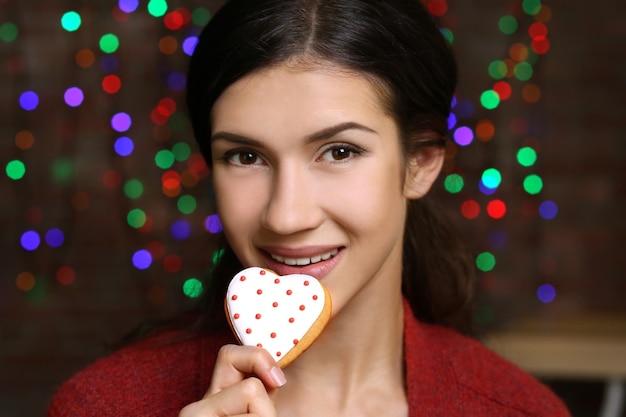 Bela jovem com saboroso biscoito de natal contra luzes desfocadas, close-up