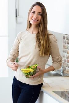 Bela jovem com salada de frutas na cozinha. Foto gratuita