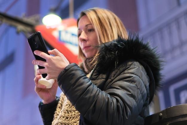 Bela jovem com smartphone e café sorrindo feliz na cidade à noite.