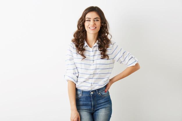 Bela jovem com sorriso sincero, estilo hippie, vestida de jeans, camisa, isolada no fundo branco, cabelos cacheados
