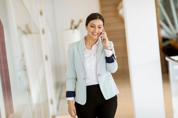 Bela jovem com telefone móvel no escritório moderno