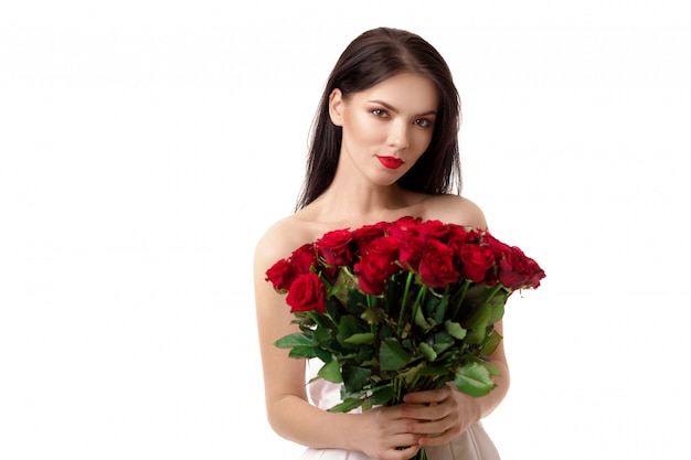 Bela jovem com um grande buquê de rosas vermelhas