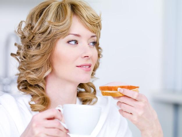 Bela jovem com um lindo sorriso fácil tomando café da manhã na cozinha