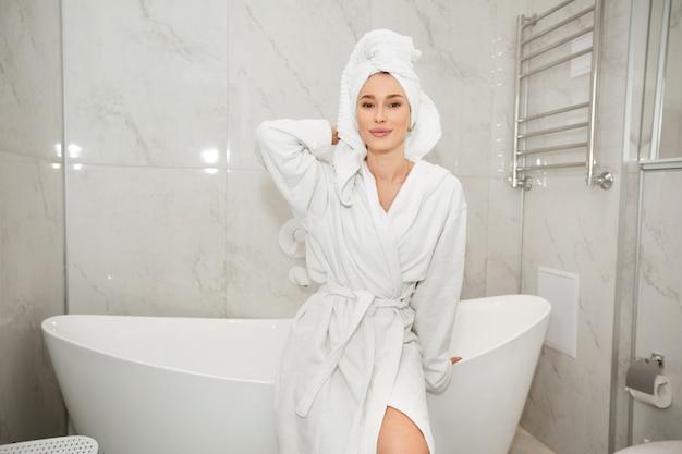 Bela jovem com um manto branco no banheiro