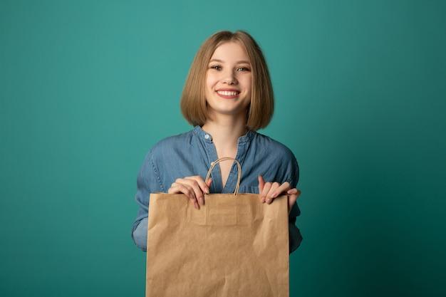 Bela jovem com um saco de papel na mão Foto Premium
