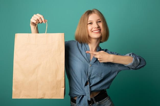 Bela jovem com um saco de papel na mão