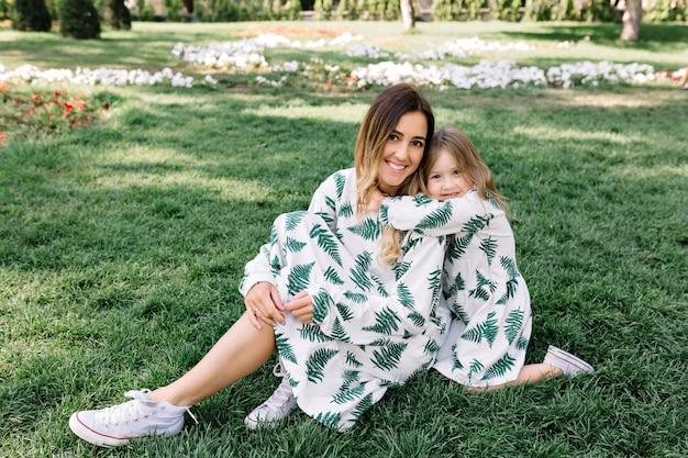 Bela jovem com uma filha está sentada na grama sob a luz do sol