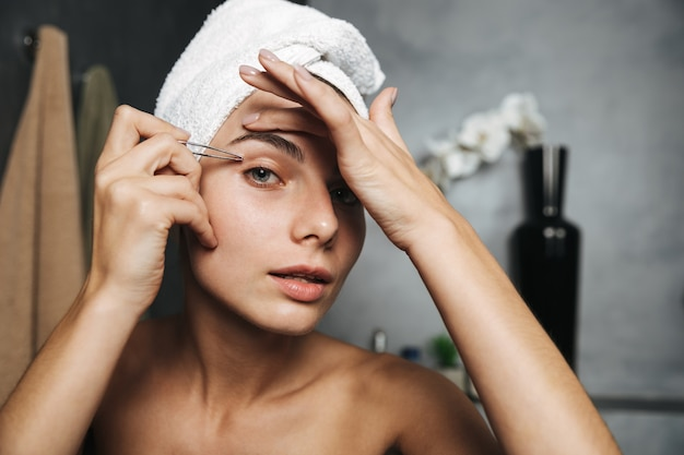 Bela jovem com uma toalha na cabeça corrigindo as sobrancelhas com uma pinça na frente do espelho no banheiro
