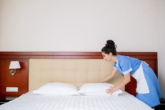 Bela jovem com uniforme de empregada doméstica em pé ao lado da cama trocando travesseiros pela manhã