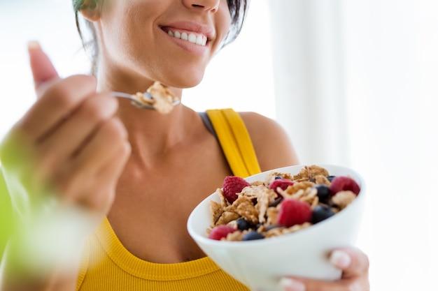 Bela jovem comendo cereais e frutas em casa.