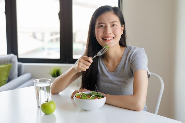 Bela jovem comendo salada
